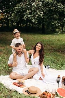Szczęśliwa matka, ojciec i ich śliczny synek mają piknik w letnim parku. dziecko siedzi na ramionach ojca. koncepcja rodziny i wypoczynku