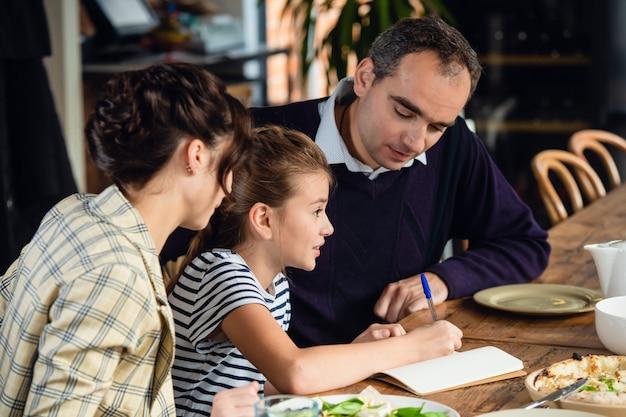 Szczęśliwa matka, ojciec i mała dziewczynka, jedząc obiad i rozmawiając w restauracji lub kawiarni