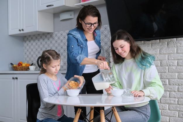 Szczęśliwa matka opiekuje się córkami w kuchni. jedzenie dziewcząt siedzących przy stole, poranne śniadanie, mleko w dzbanku i słodkie płatki kukurydziane