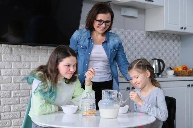 Szczęśliwa matka opiekuje się córkami w kuchni