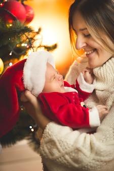 Szczęśliwa matka patrząc na chłopca ubranego w ubrania mikołaja