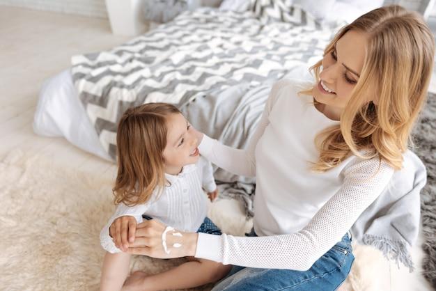 Szczęśliwa matka pieści swoją córeczkę trzymając się za ręce, mając uśmiechniętą buźkę pomalowaną kremem na własnej dłoni