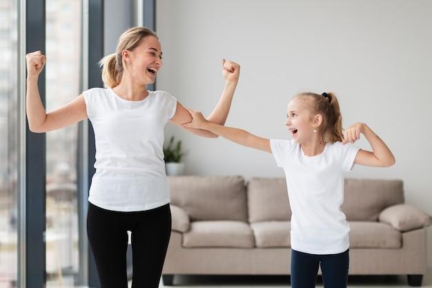 Szczęśliwa matka pokazuje daleko bicepsy smiley córka
