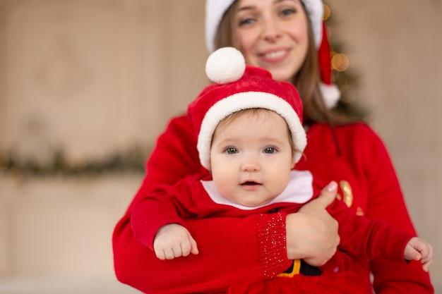Szczęśliwa matka przytula córeczkę w czerwonym stroju mikołaja i kapeluszu, w pobliżu choinki.