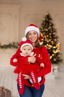 Szczęśliwa matka przytula córeczkę w czerwonym stroju świętego mikołaja i czapce, w pobliżu choinki.