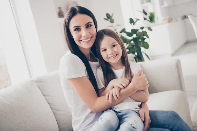Szczęśliwa matka przytulić dziecko dziewczyna siedzi sofa w pokoju w pomieszczeniu