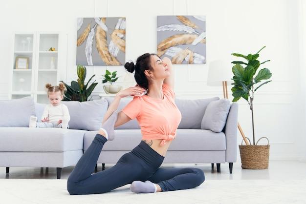 Szczęśliwa matka robi rankowi ćwiczy w joga pozie podczas gdy jej mała córka bawić się w domu. młoda urocza mama zabawy ćwiczyć medytację relaksujący weekend bez stresu z córeczką.