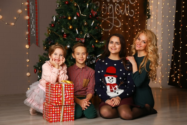 Szczęśliwa matka rodziny i dzieci na boże narodzenie na choince z prezentami.