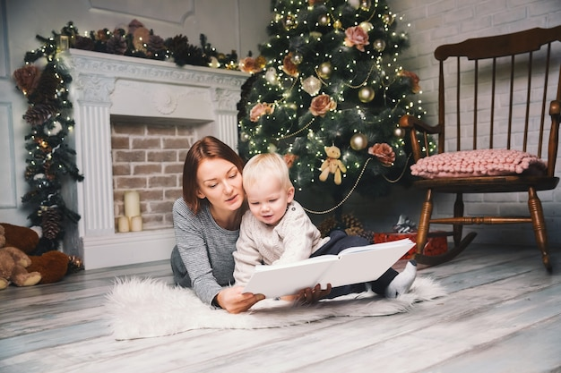Szczęśliwa matka rodziny z dzieckiem wśród świątecznych ozdób czytająca historię w książce