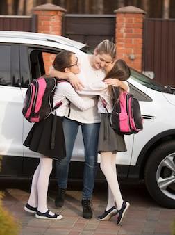 Szczęśliwa matka spotyka córki w pobliżu samochodu po lekcjach w szkole