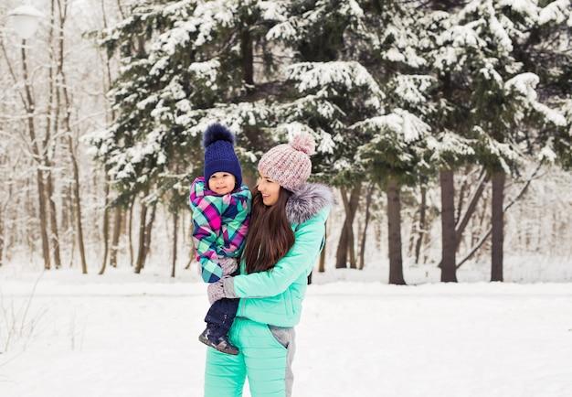 Szczęśliwa matka trzyma córeczkę na spacer w zimowym śnieżnym lesie.