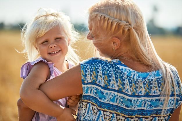 Szczęśliwa matka trzyma dziecko uśmiecha się na polu pszenicy w słońcu.
