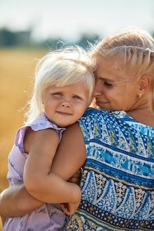 Szczęśliwa matka trzyma dziecko uśmiecha się na polu pszenicy w słońcu