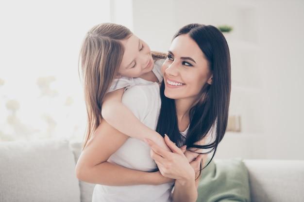 Szczęśliwa matka trzymać na barana córeczkę w salonie domu w pomieszczeniu