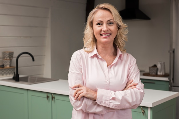 Szczęśliwa matka uśmiecha się i pozuje w kuchni