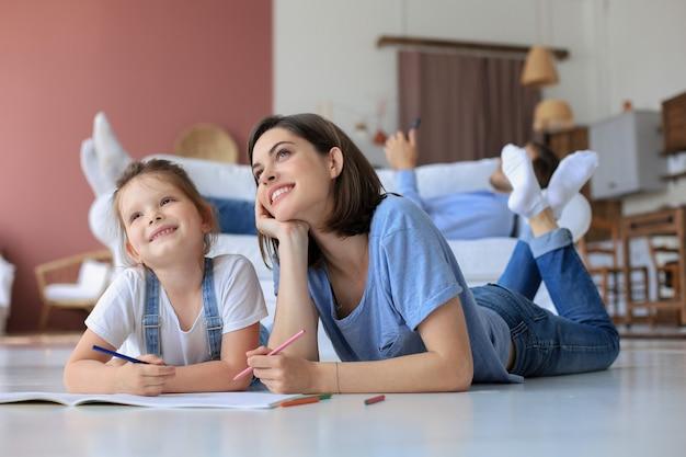 Szczęśliwa matka uśmiechnięta córka leżąc na ciepłej podłodze ciesząc się twórczą aktywnością, rysując ołówkiem, kolorując zdjęcia w albumach, ojciec odpoczywa na kanapie, rodzina spędza razem wolny czas.