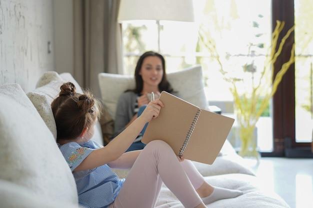 Szczęśliwa matka uśmiechnięta córka siedzi na kanapie ciesząc się aktywnością twórczą, rysując piórem zdjęcia w albumach, matka i córka spędzają razem wolny czas.