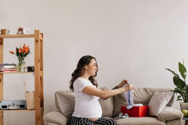 Szczęśliwa matka w białej koszulce i spodniach patrzy na swoje przyszłe ubrania dla dzieci