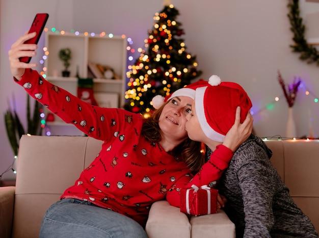 Szczęśliwa matka w czapce mikołaja i synek w czapce mikołaja z prezentem całuje matkę siedzącą na kanapie robi selfie przy użyciu smartfona bawiąc się w urządzonym pokoju z choinką w tle
