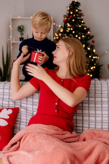 Szczęśliwa matka w czerwonej sukience siedzi na kanapie uśmiechając się, podczas gdy jej małe dziecko stoi za nią, dając prezent matce w udekorowanym pokoju z choinką w ścianie