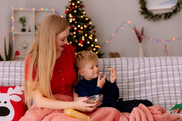 Szczęśliwa matka w czerwonej sukience z małym dzieckiem pod kocem karmienie dziecka ciasteczkami w urządzonym pokoju z choinką w tle