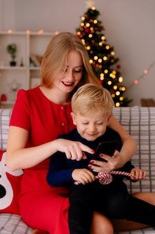 Szczęśliwa matka w czerwonej sukience z małym dzieckiem siedzi na kanapie ze smartfonem w urządzonym pokoju z choinką w tle
