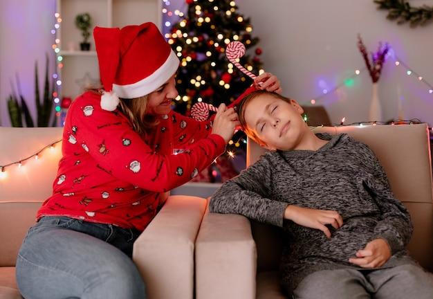 Szczęśliwa matka w santa hat zakładająca zabawną obwódkę na głowę śpiącego syna siedzącego na kanapie w udekorowanym pokoju z choinką w ścianie