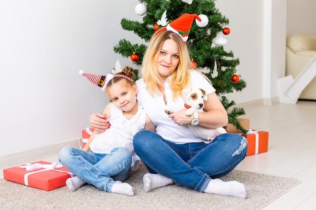 Szczęśliwa matka z córką i psem jack russell terrierem siedzącym przy choince
