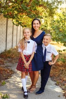 Szczęśliwa matka z dwójką uczniów po szkole