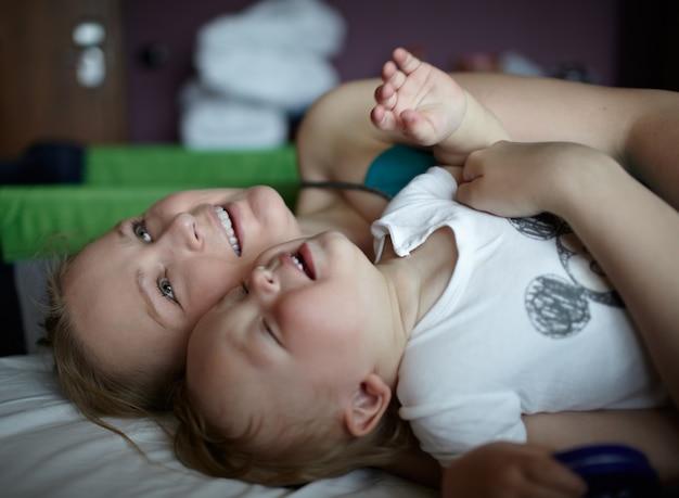 Szczęśliwa matka z dzieckiem w pokoju hotelowym