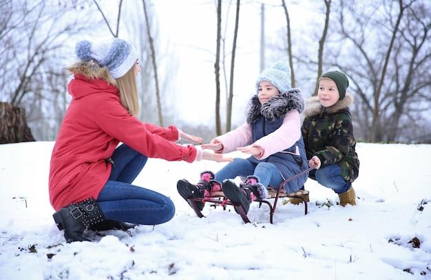 Szczęśliwa matka z dziećmi na sankach w zaśnieżonym parku na ferie zimowe