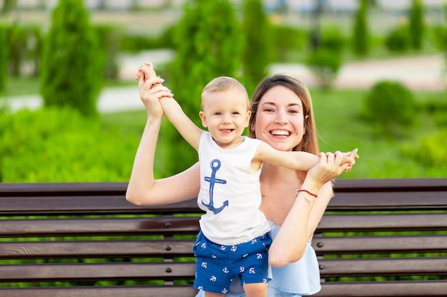Szczęśliwa matka z synkiem w parku siedzi na ławce na świeżym powietrzu i bawi się z dzieckiem w ramionach