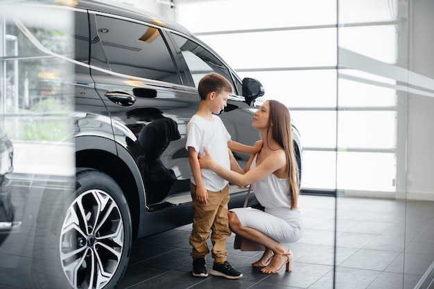 Szczęśliwa matka z synkiem wybiera nowy samochód w salonie samochodowym. kupowanie samochodu.