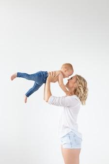 Szczęśliwa matka z uroczym dzieckiem na białej ścianie