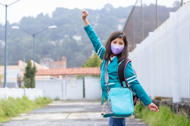 Szczęśliwa meksykańska dziewczyna podekscytowana powrotem do szkoły nosząca maskę ochronną po zamknięciu koronawirusa