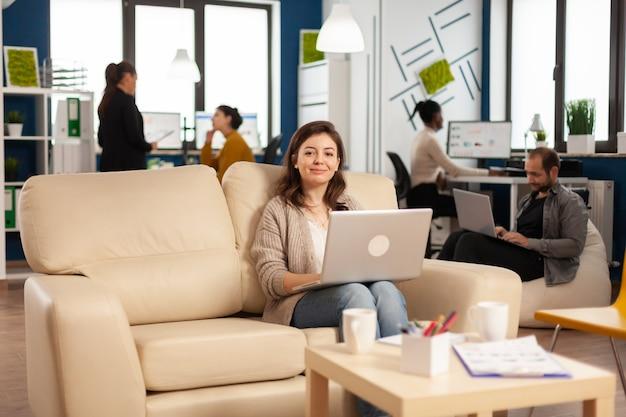 Szczęśliwa menedżerka kobieta siedzi na kanapie przed kamerą, uśmiechając się, trzymając laptopa, podczas gdy w tle pracują różnorodni koledzy