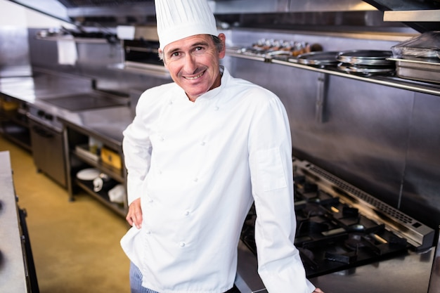 Szczęśliwa męska szef kuchni pozycja w handlowej kuchni