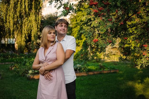Szczęśliwa męża i żony pozycja w zielonym parku pod gałąź