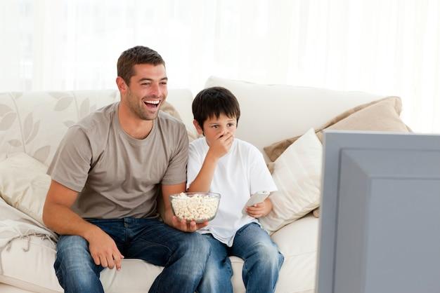 Szczęśliwa mężczyzna dopatrywania telewizja z jego syna obsiadaniem na kanapie