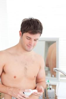 Szczęśliwa mężczyzna kładzenia shavingfoam pozycja w jego łazience