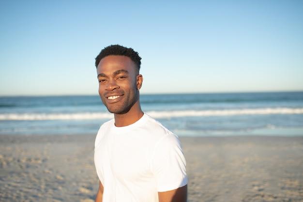 Szczęśliwa mężczyzna pozycja na plaży