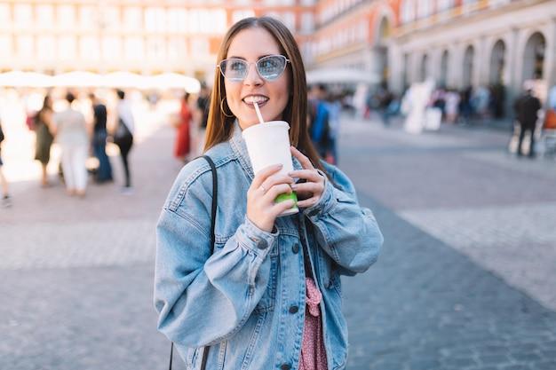 Szczęśliwa miastowa kobieta z błękitnymi okularami przeciwsłonecznymi cieszy się jej ranek pije sodę w styrofoam filiżance z słomą. ładna dziewczyna na ulicy. zabierz napoje.