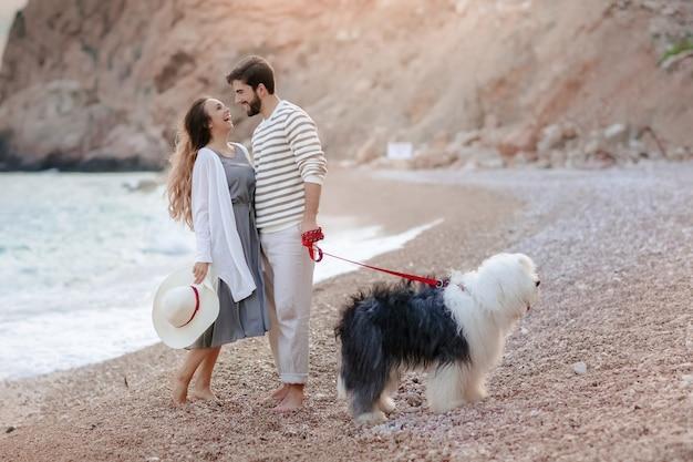 Szczęśliwa międzyrasowa młoda para z psem