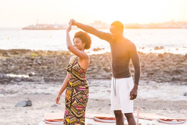 Szczęśliwa, miła, piękna, czarna para rasy afrykańskiej, ciesz się i tańcz nad morzem podczas złotego zachodu słońca na świeżym powietrzu