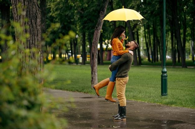 Szczęśliwa miłość para obejmując w letni deszczowy dzień. mężczyzna i kobieta przytula się pod parasolem w deszczu, romantyczna randka na ścieżce spacerowej, deszczowa pogoda w alei