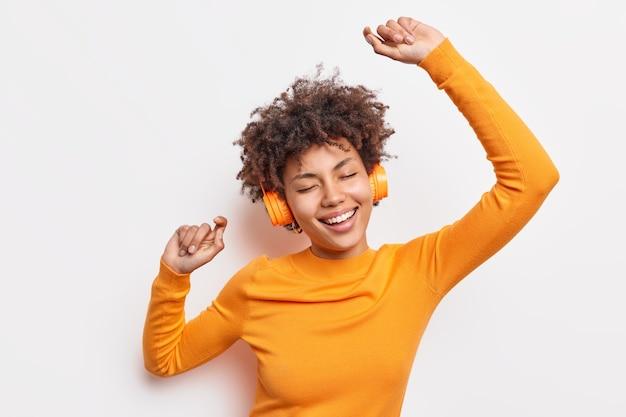 Szczęśliwa młoda afro amerykanka porwana muzyką tańczy beztrosko z podniesionymi rękami, ma zamknięte oczy, nosi słuchawki stereo na uszach, ubrana w pomarańczowy sweter na białym tle nad białą ścianą