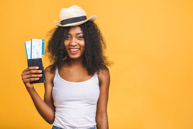 Szczęśliwa młoda afroamerykanin czarna kobieta z biletami lotniczymi