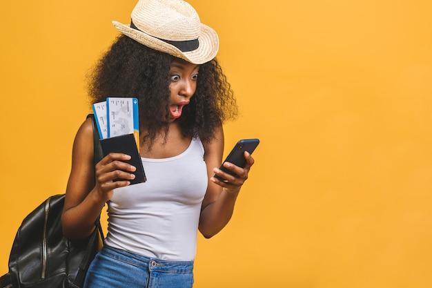 Szczęśliwa młoda afroamerykanin murzynka z biletów lotniczych przy użyciu telefonu