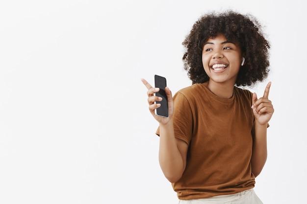 Szczęśliwa młoda afroamerykańska tancerka w brązowej koszulce słuchająca muzyki w bezprzewodowych słuchawkach dousznych tańcząca i poruszająca palcami w rytm trzymając smartfon wpatrując się w lewo z uśmiechem