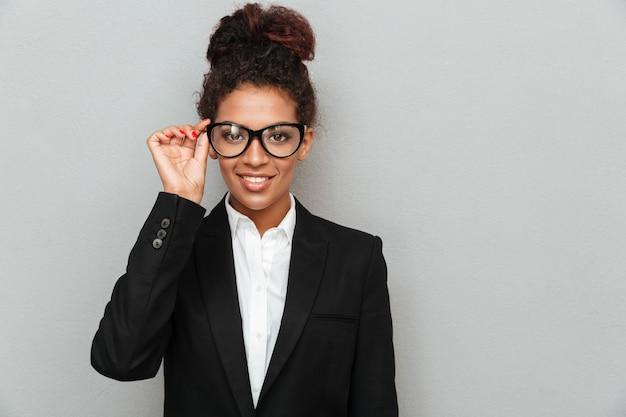Szczęśliwa młoda afrykańska biznesowa kobieta jest ubranym szkła